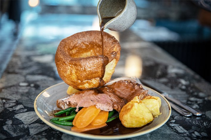 Roast sirloin with with green beans, carrots, roast potatos, gravy and a yorkshire pudding. Craft beer pub, Sussex.